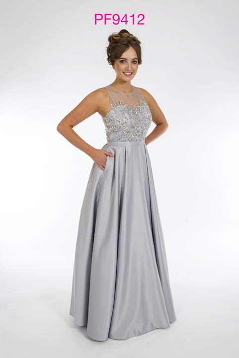 Prom girl wearing silver satin princess gown with beaded illusion bodice and full skirt with pockets.