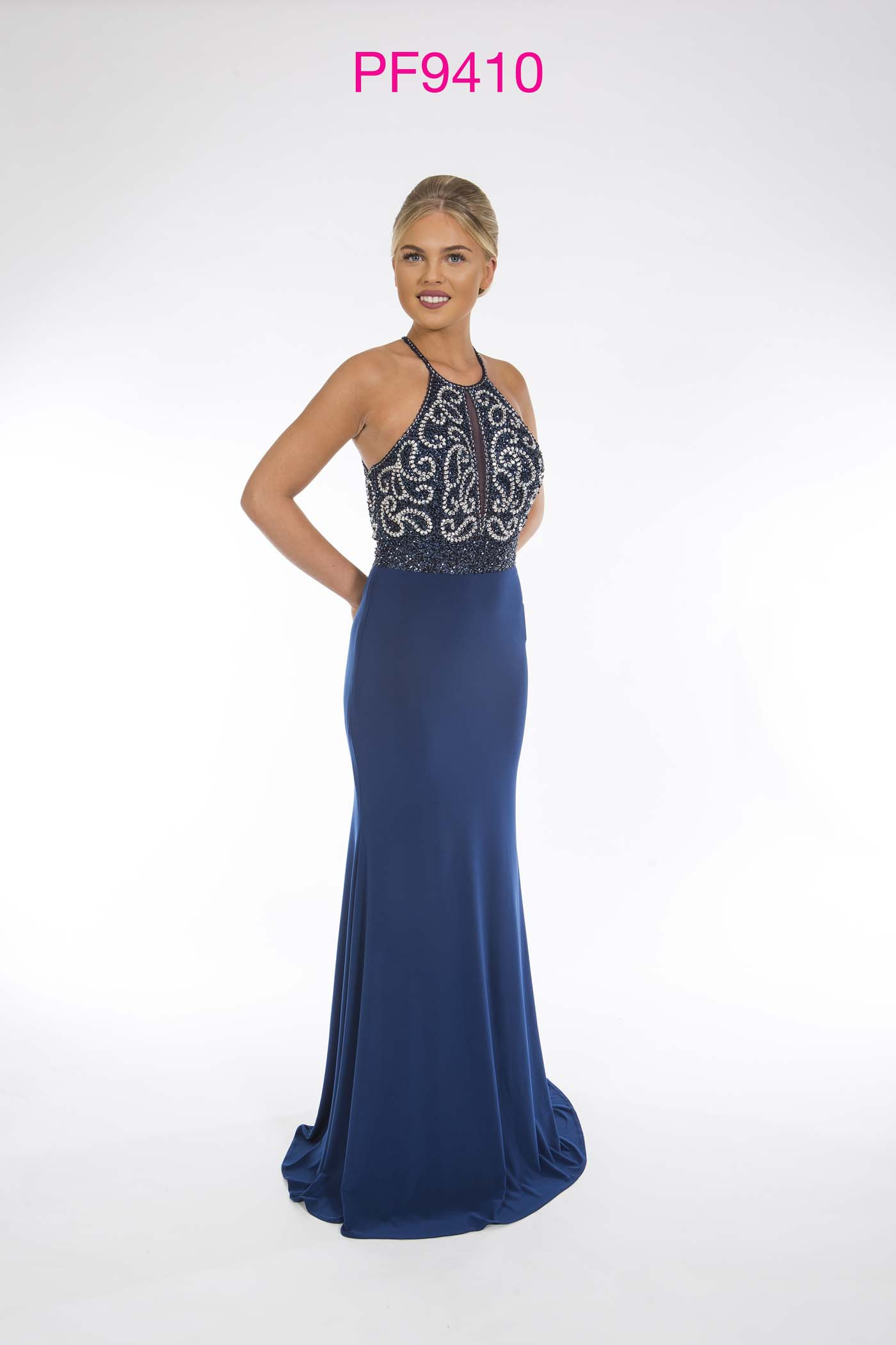 Prom girl wearing french navy fitted jersey gown with sliver beaded top and cross over straps at back.