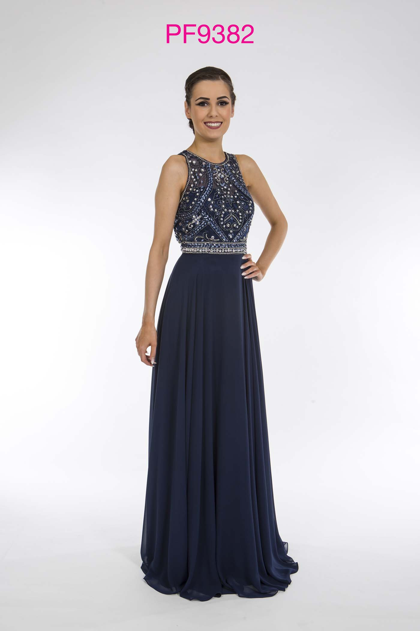 Prom girl wearing navy chiffon full length gown with full skirt and silver beaded bodice.
