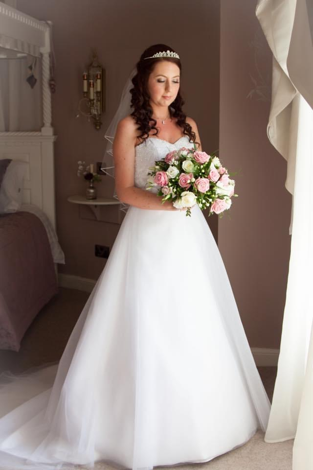 Bride wearing a white Aline gown with beaded sweetheart bodice and soft tulle skirt.