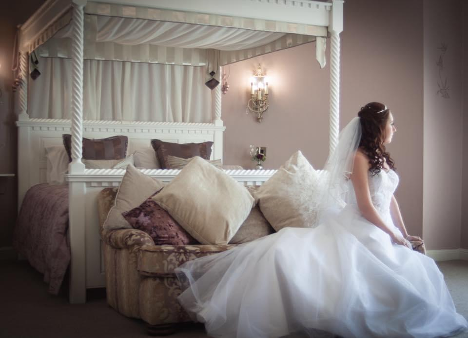 A brides seated at the foot of a four poster bed ready for her ceremony.