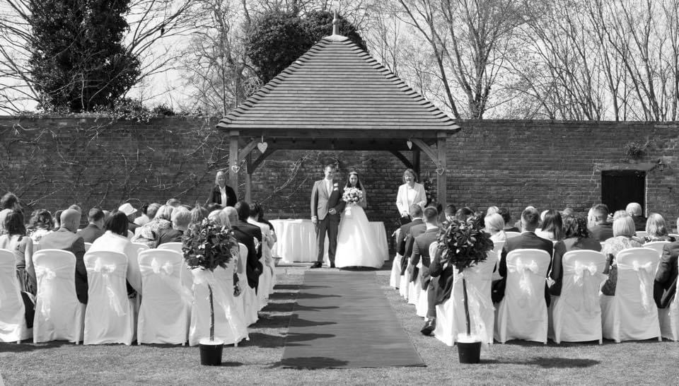 Bride and Groom having their wedding ceremony in the walled garden at Hatherey Manor Gloucester.
