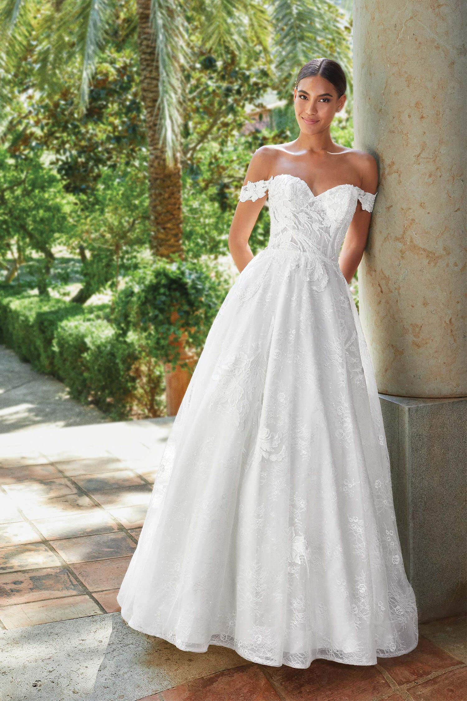 A bride wearing a princess style gown with sweetheart neckline and lace arm swags.