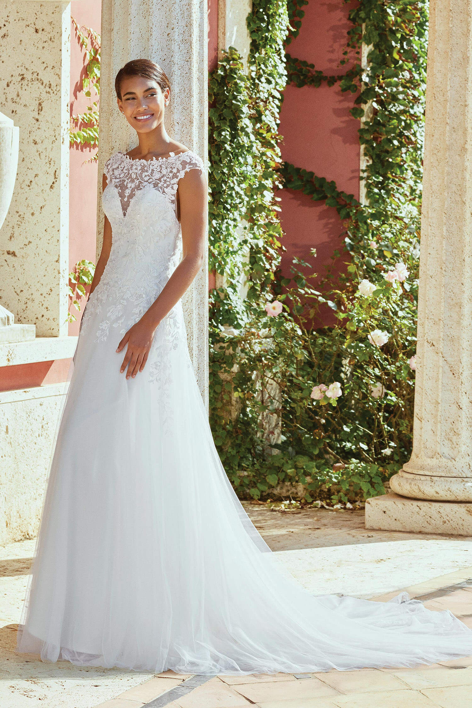 A bride wearing a fit and flare style gown with illusion neckline and soft drape tulle skirt. The gown is covered in sparkling beaded appliques.