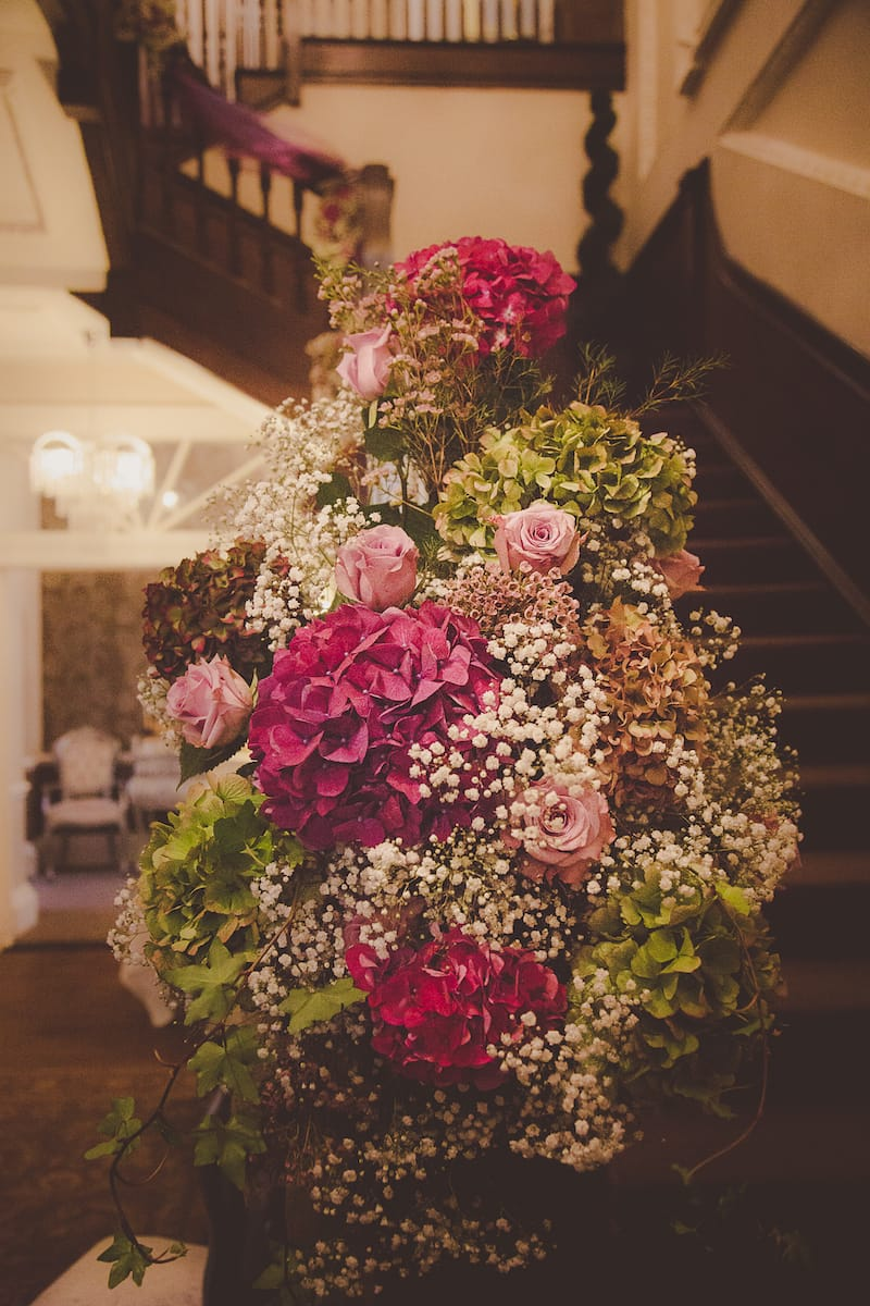 A Staircase decorated with burgundy and pink floral decorations Ready for a wedding ceremony..