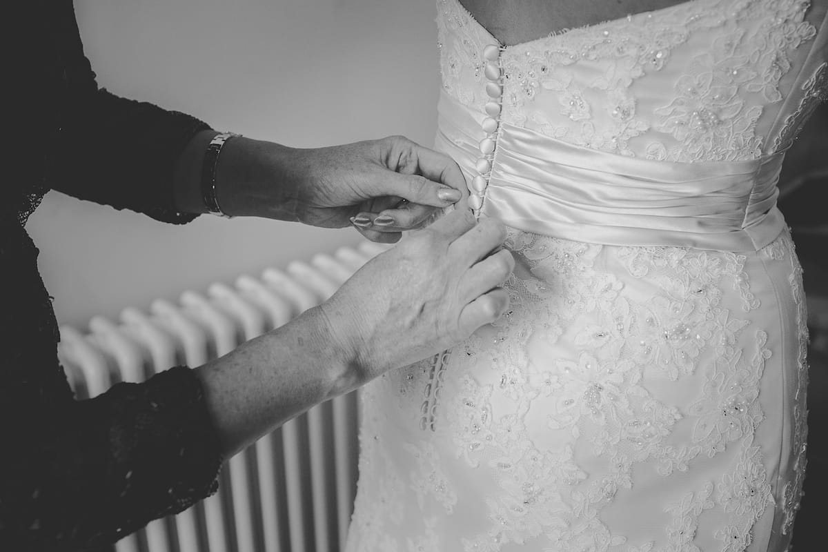 Bride being fastened into her buttoned back wedding dress