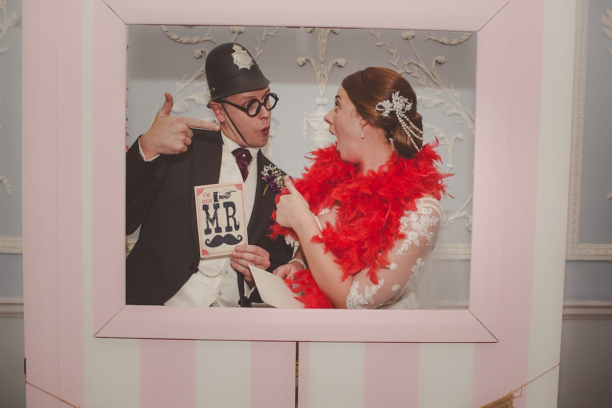Bride and Groom in a photo booth dresses in fancy dress.