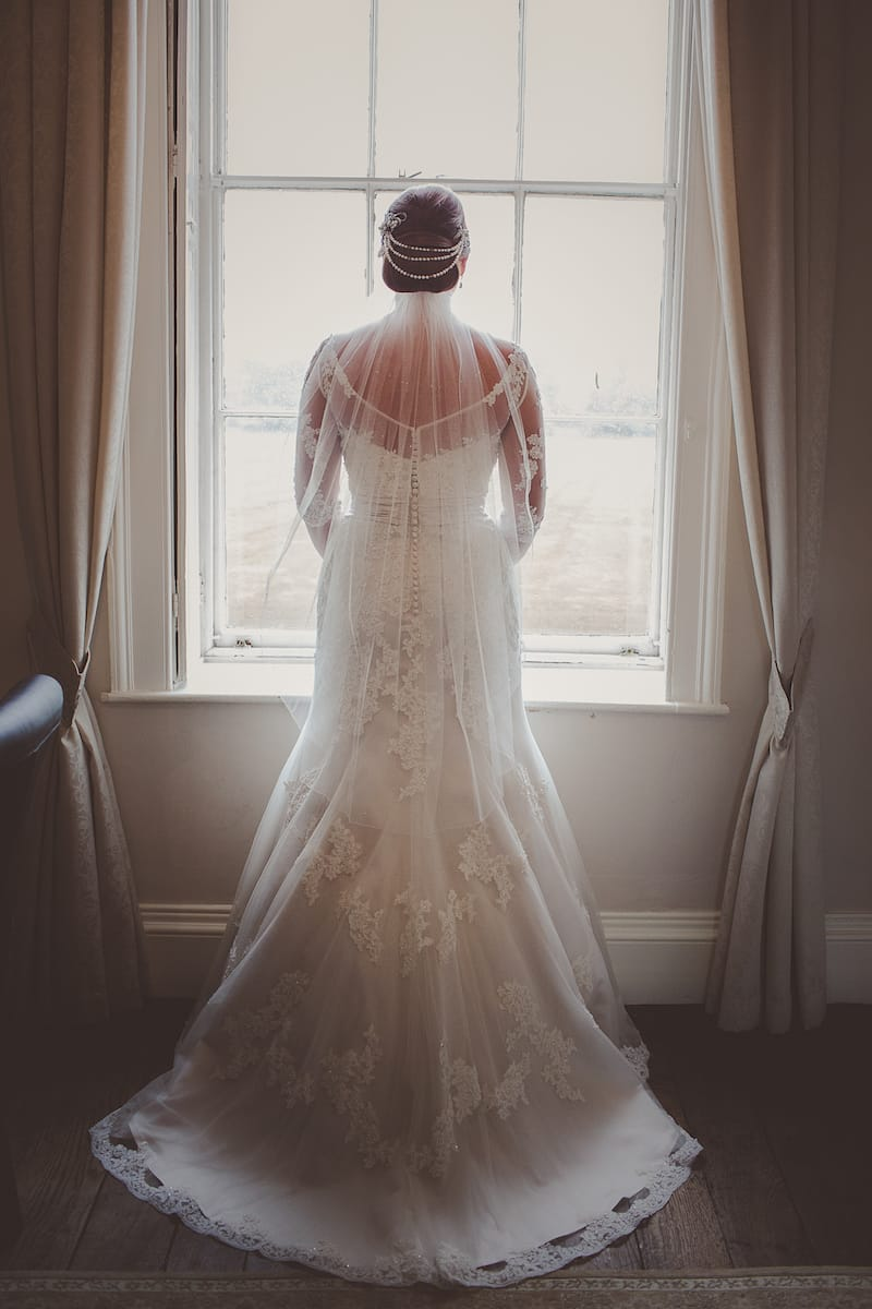 Bride ready for her ceremony, wearing an oyster coloured gown with hip length veil