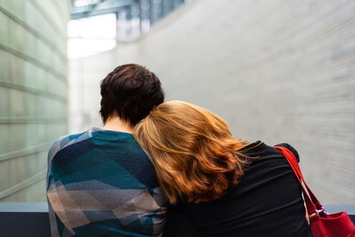 A couple facing away from you, the lady rests her head on her partners shoulder for comfort.t