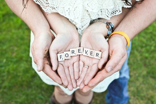 A couple wtih cupped hands holding a sign that says forever.