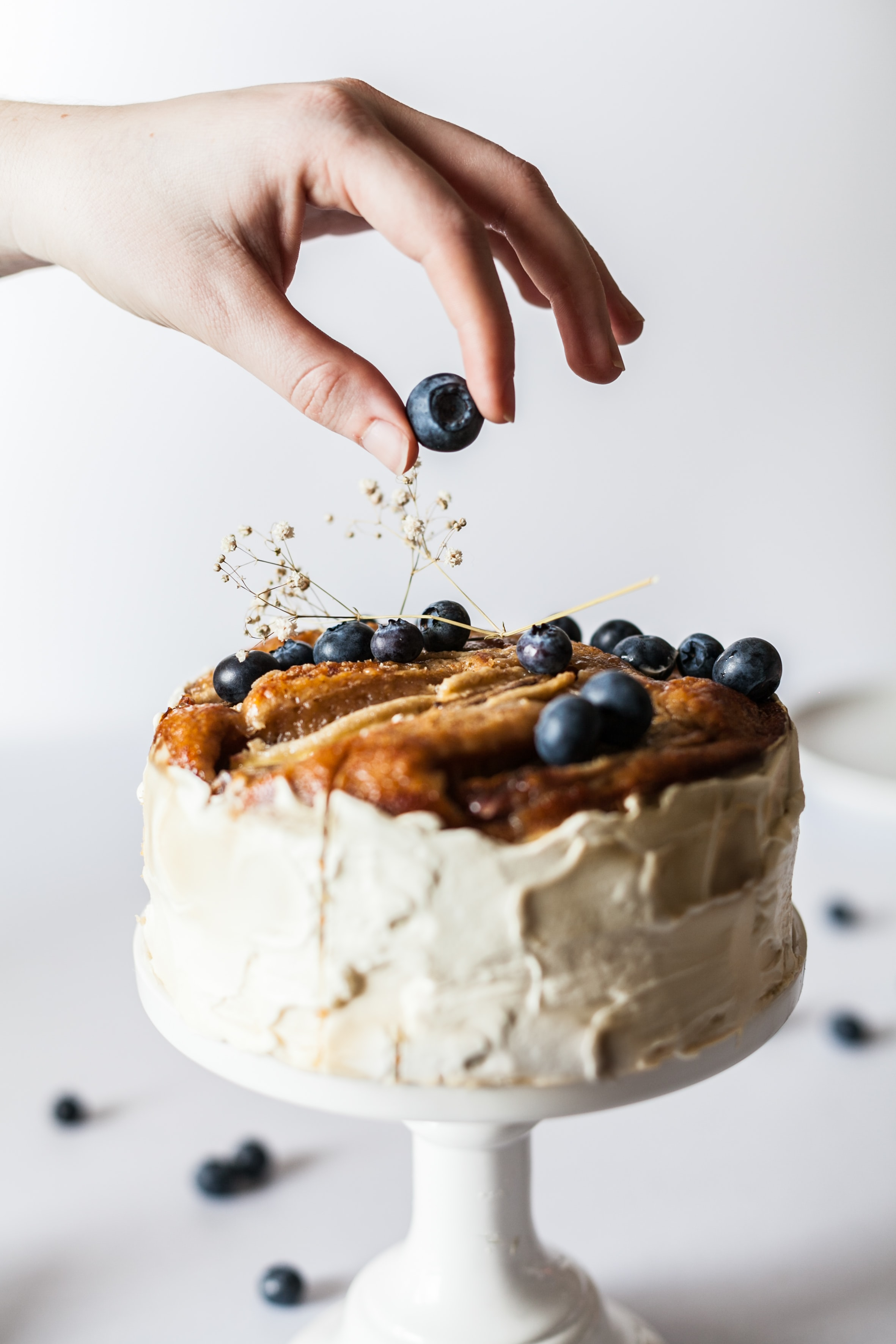 lady decorating a homemade cake with blueberries