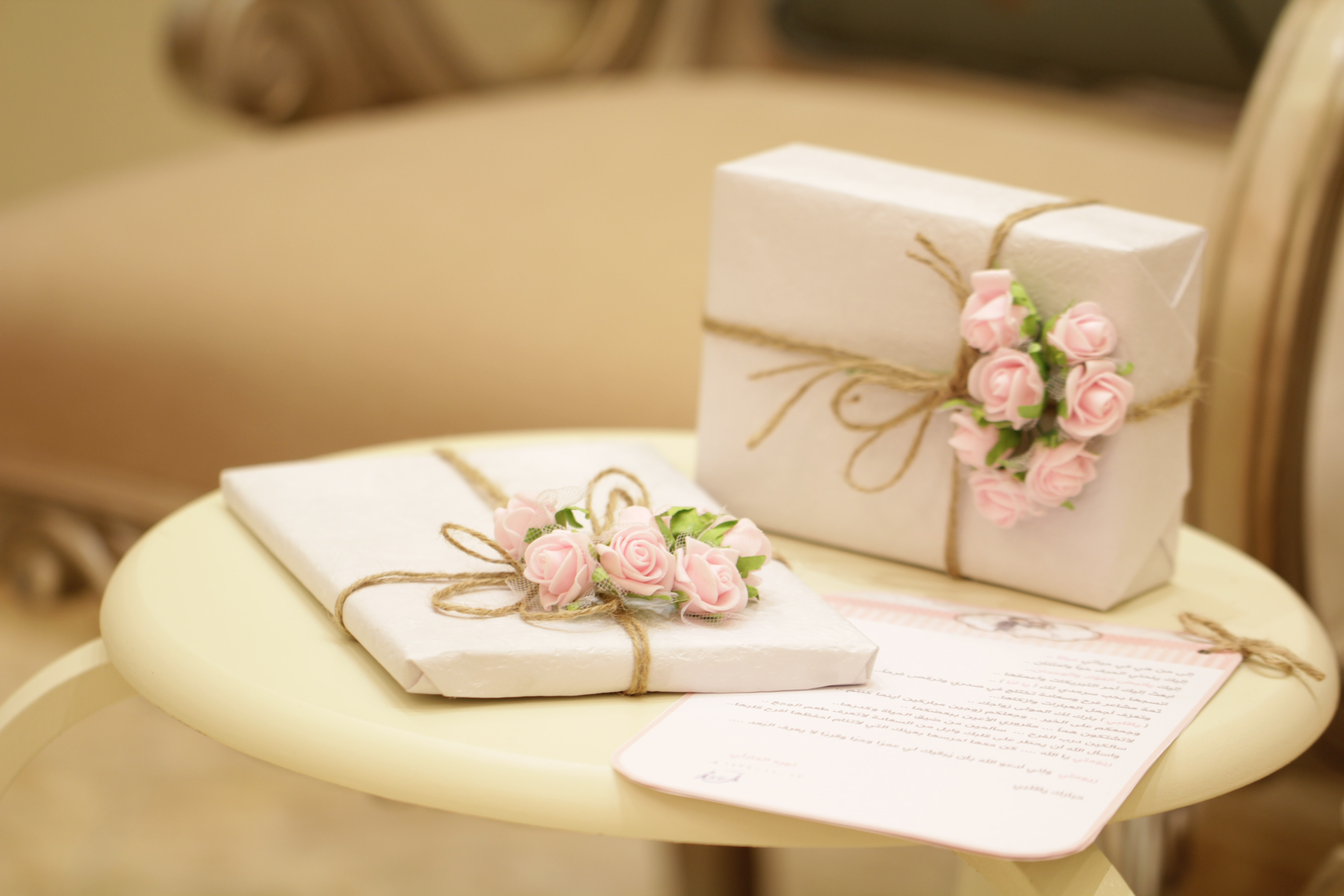 A pair of wedding gifts wrapped in paper and tied with string with tiny pink roses.