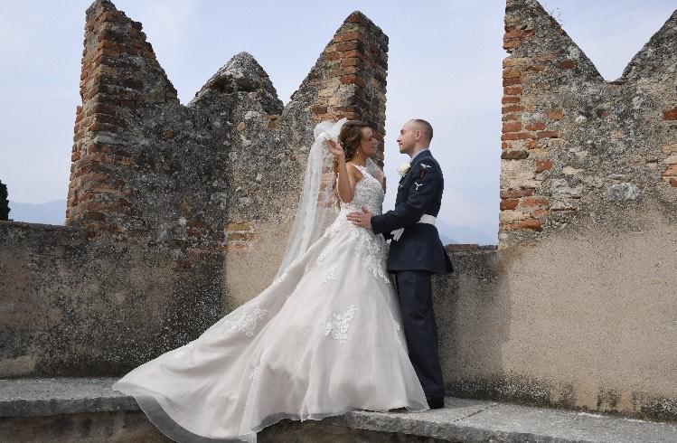 Bride and groom posing near some battlements in Lake Garda