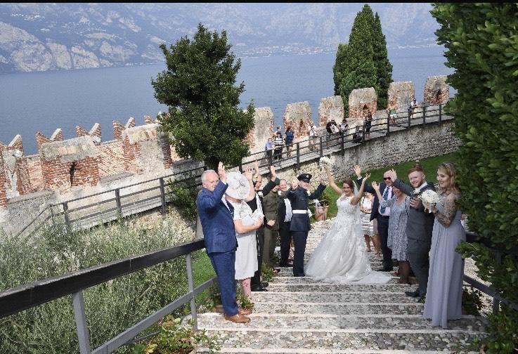 Bride and military groom on the steps overlooking Lake Garda.