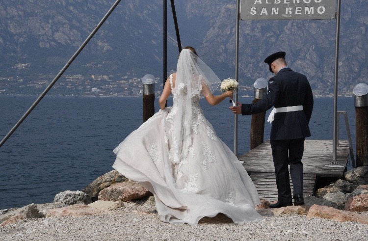 Bride and groom walking on a jetty over Lake Garda.
