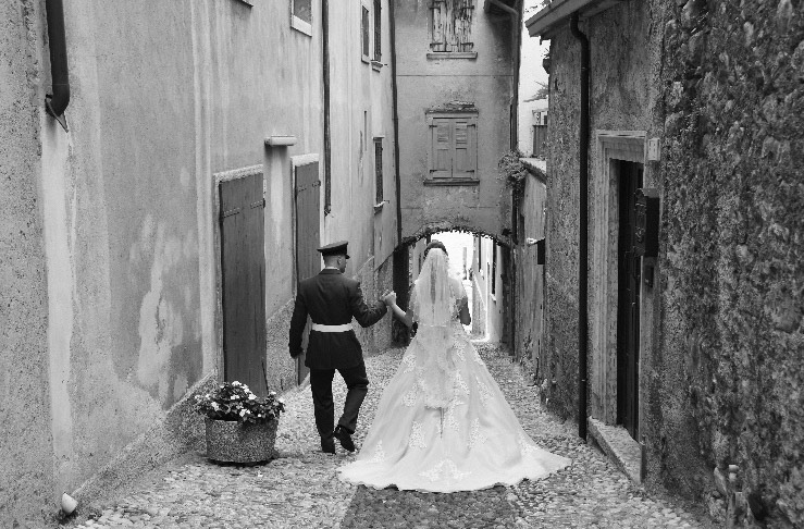 Bride and grrom strolling down a cobbled street in Lake Garda, Italy