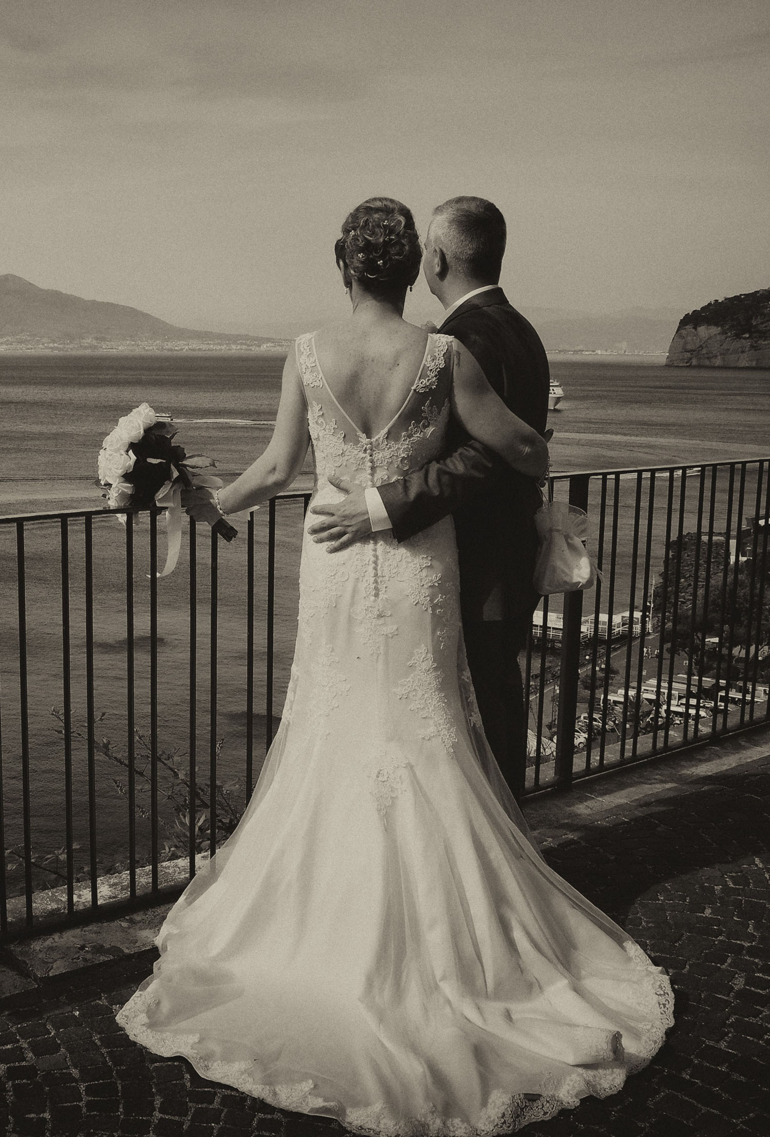 Bride and Groom standing by some iron railings overlooking the sea in Sorrento Italy.