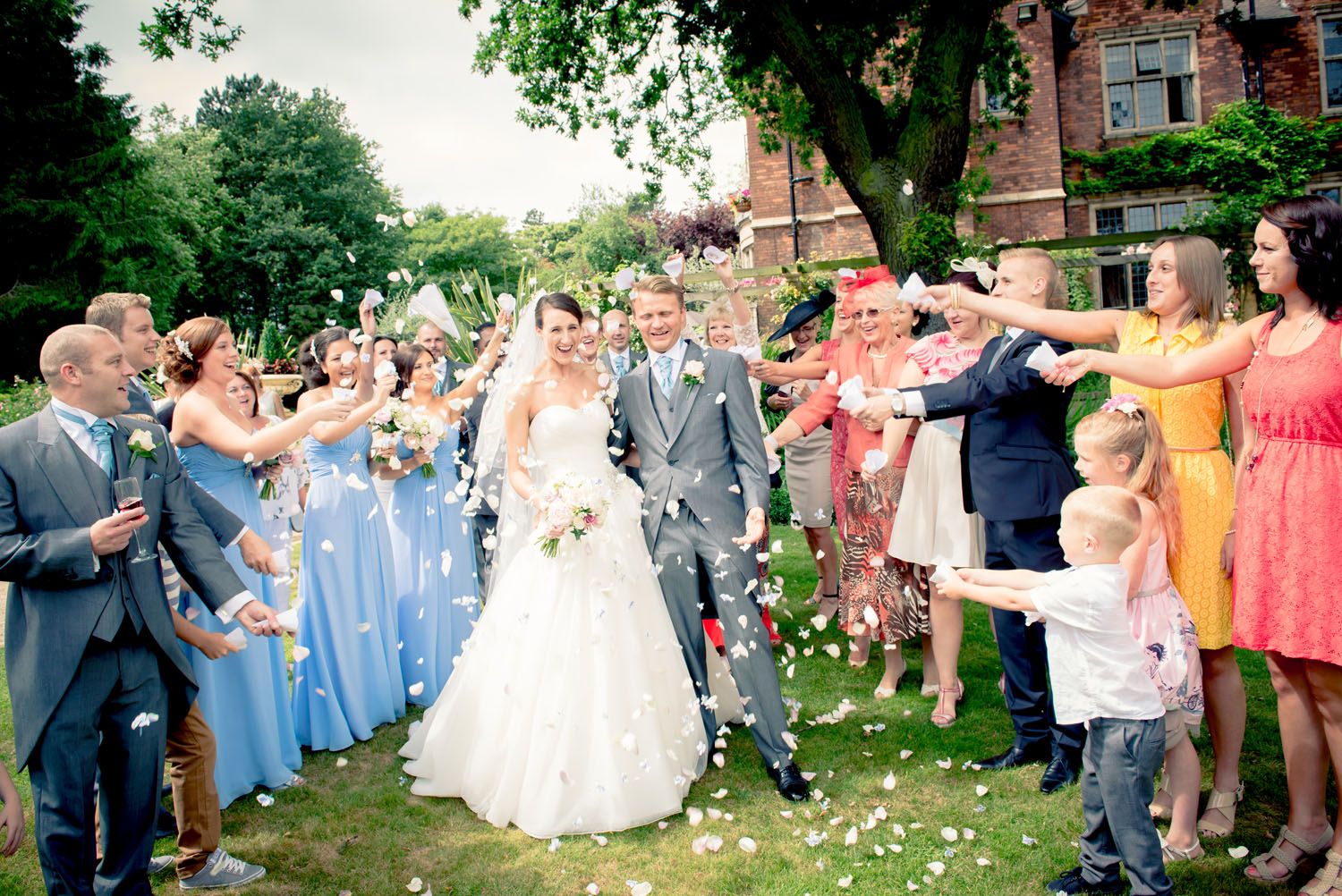 Bride and Groom being scattered in confetti by their gusts.