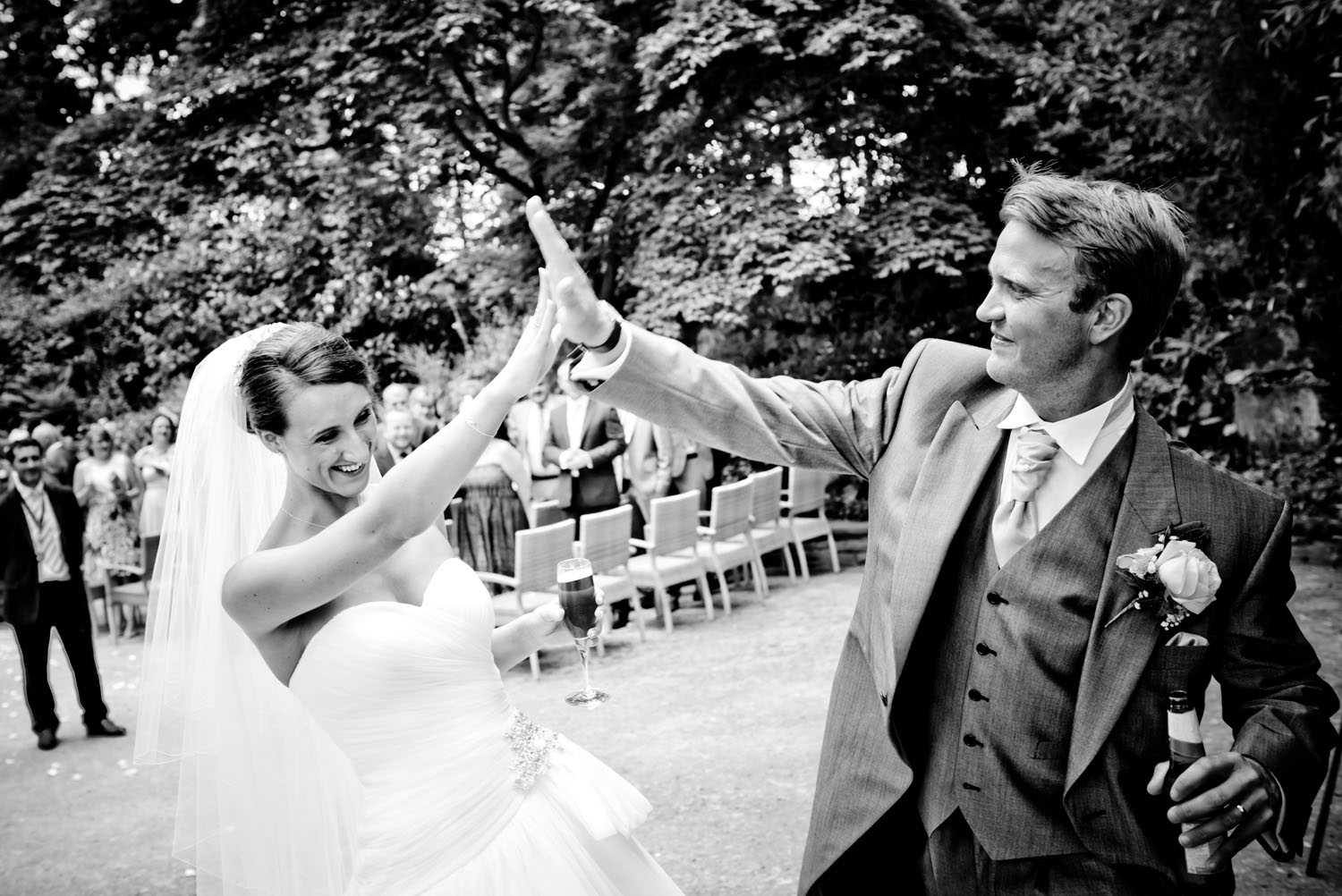 Bride and groom celebrating their outdoor wedding with a high five, while guest look on b hind them