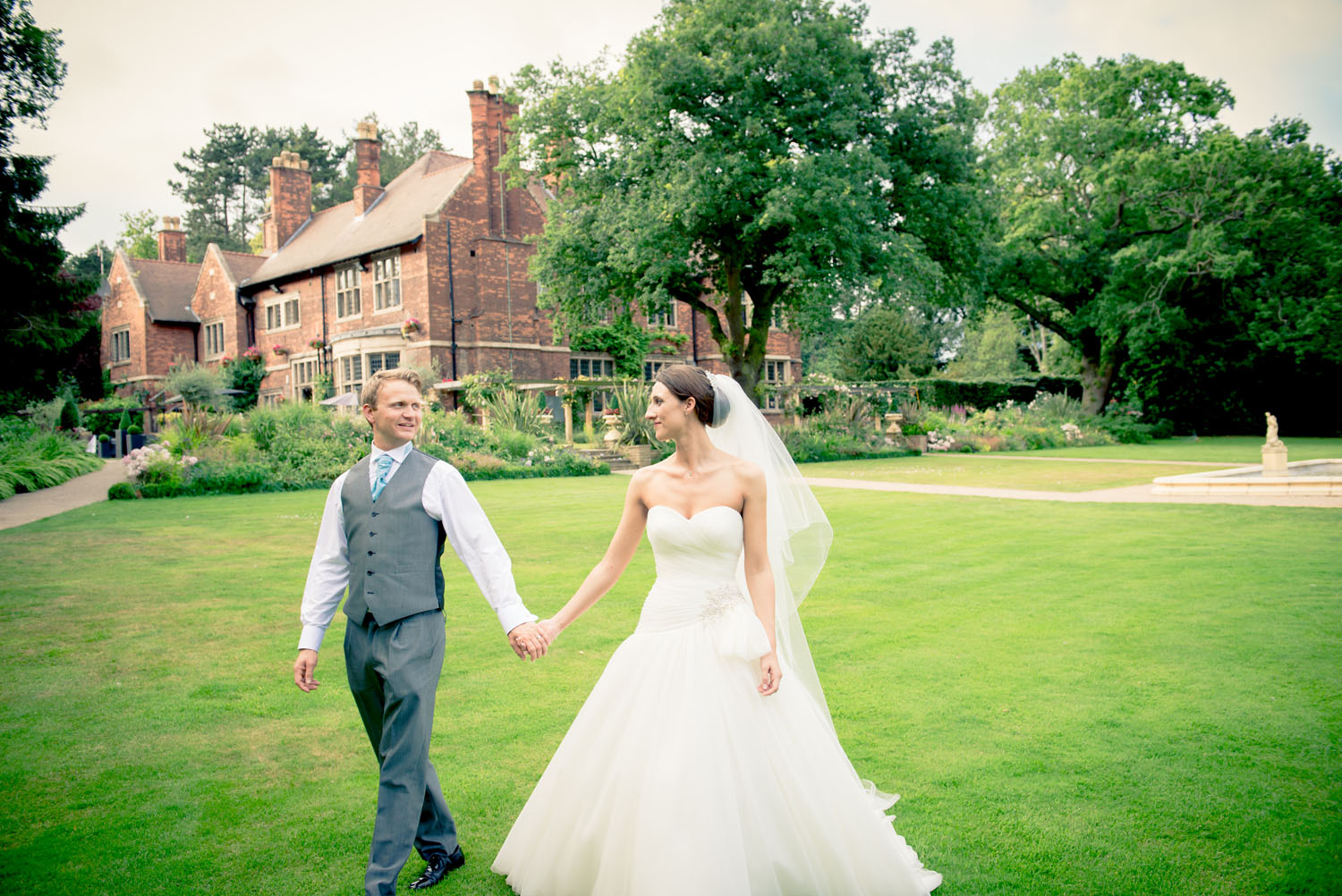 Bride and Groom waling together in the grounds of a hotel.