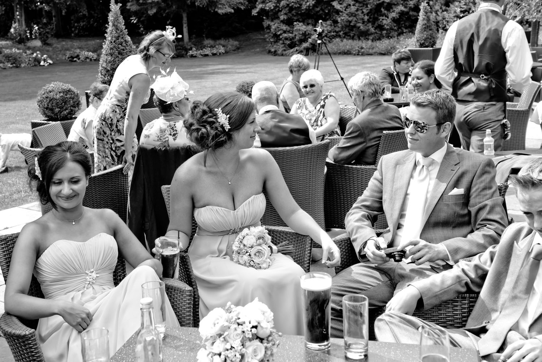Wedding guests enjoying the summer sunshine together.