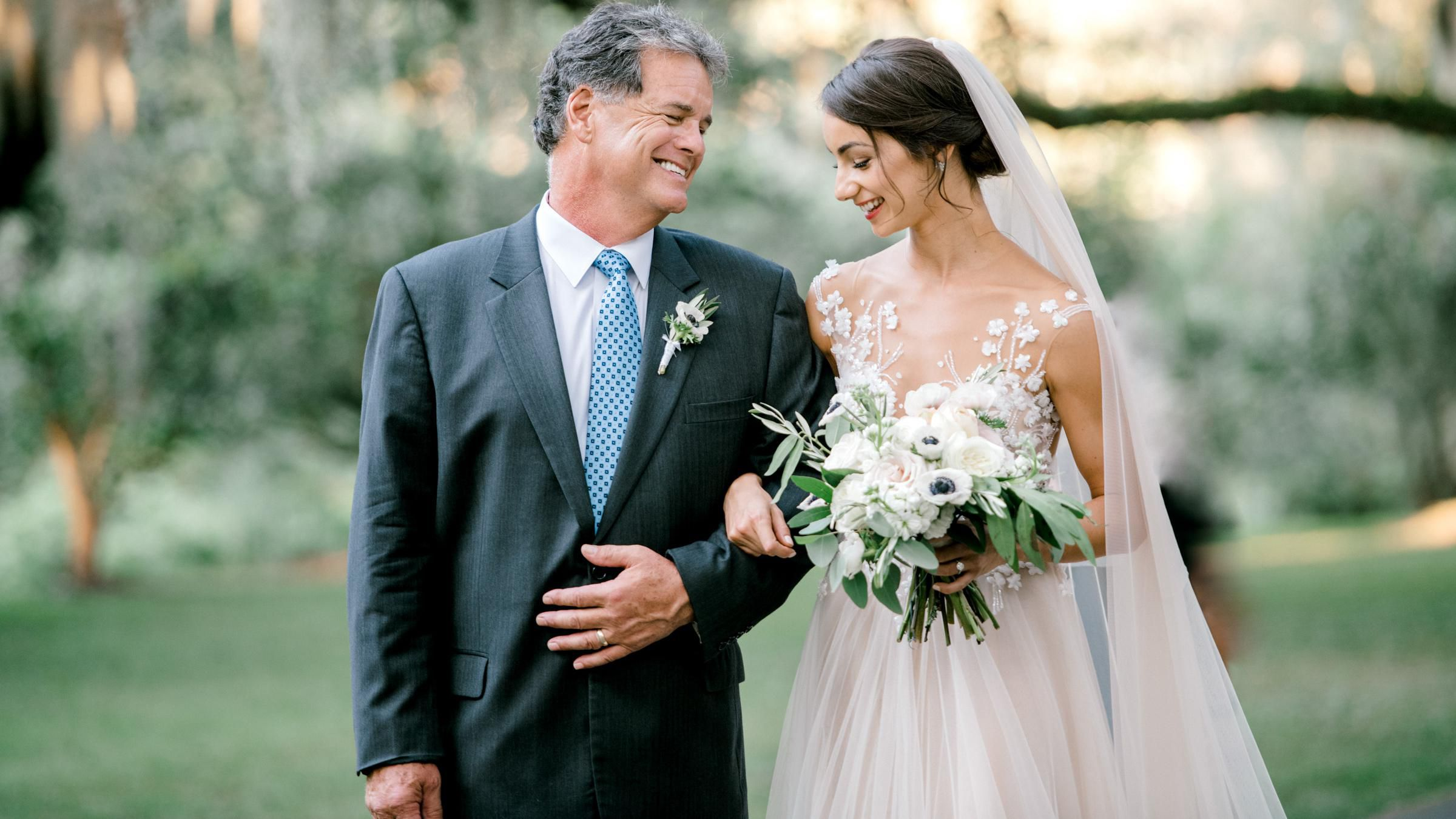A Bride and her Father smiling at each other on her wedding day.