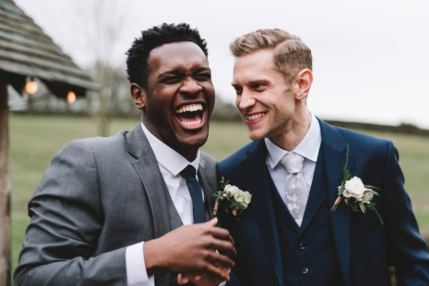 A Groom and his Best Man laughing and sharing a joke.