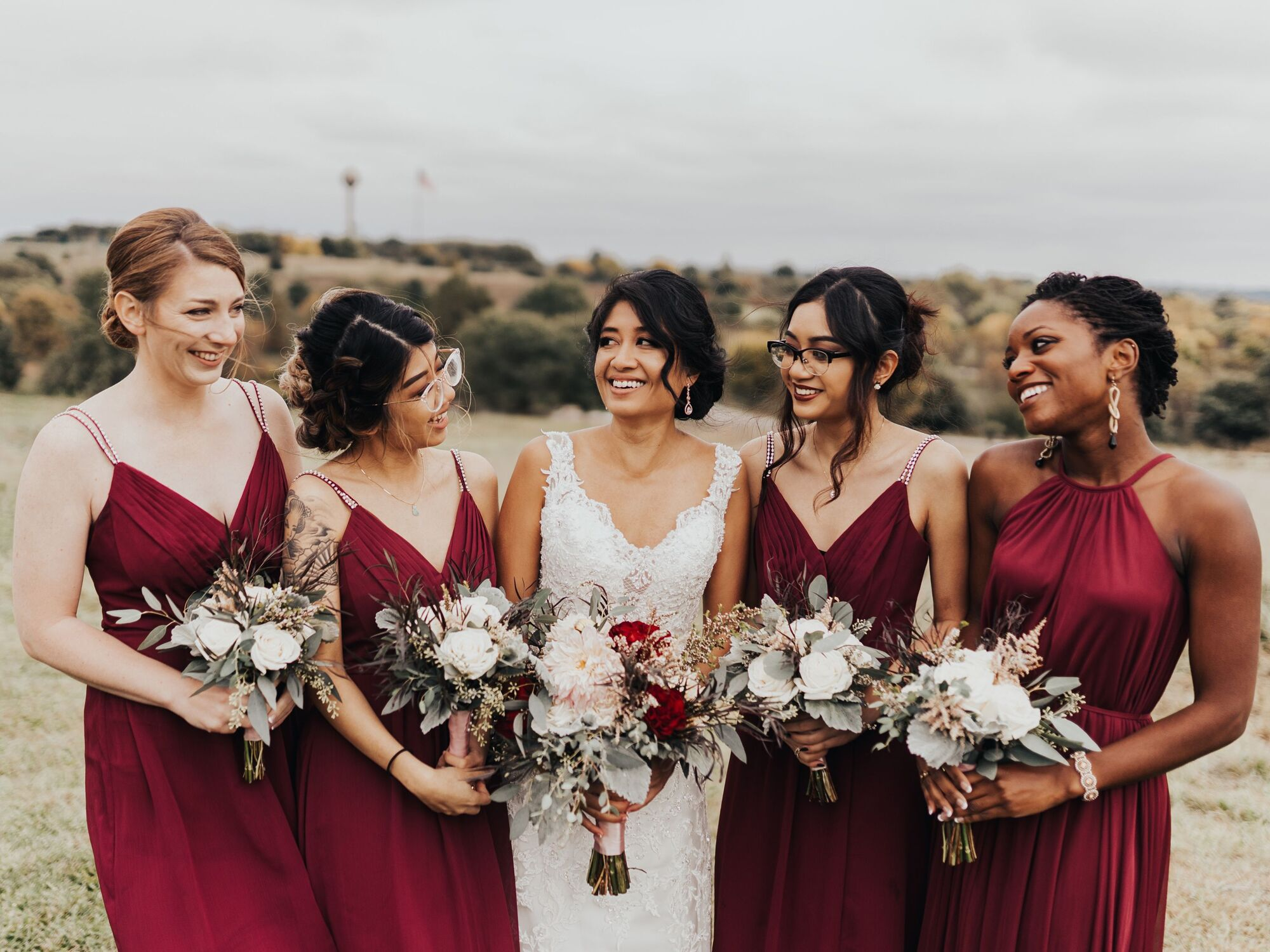 Bride in her ivory wedding dress with 4 bridesmaids in burgundy red.
