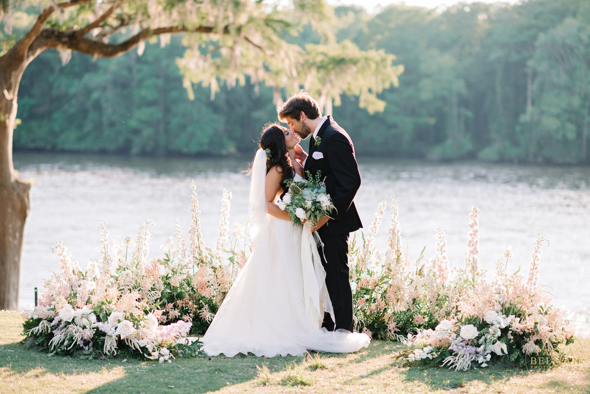 A bride and groom by a lake kissing