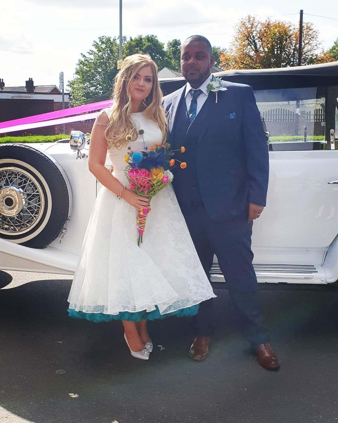 Bride and Groom next to their vintage car arriving at the church