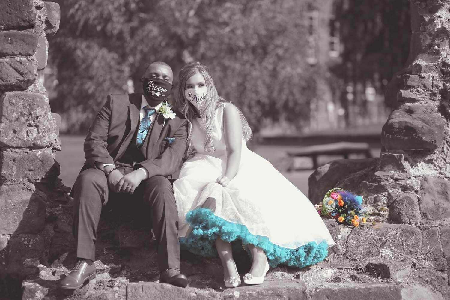 Bride and Groom sitting side by side wearing face masks.
