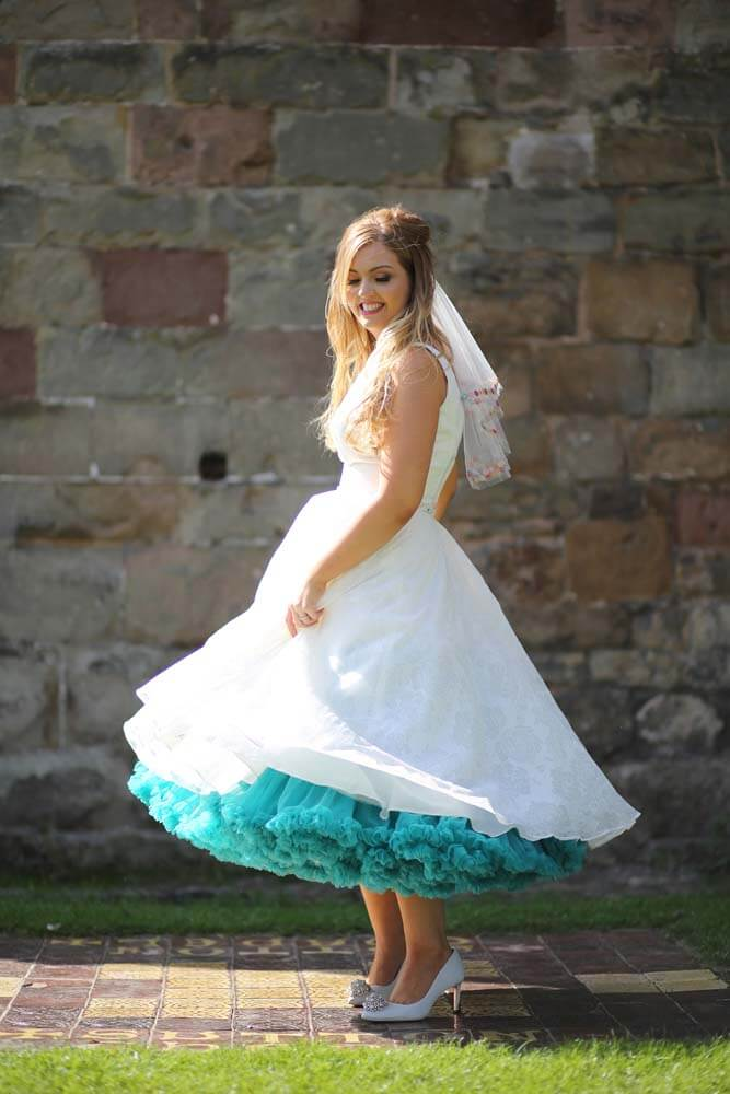 Bride wearing a 50's style tea length dress with teal underskirt.