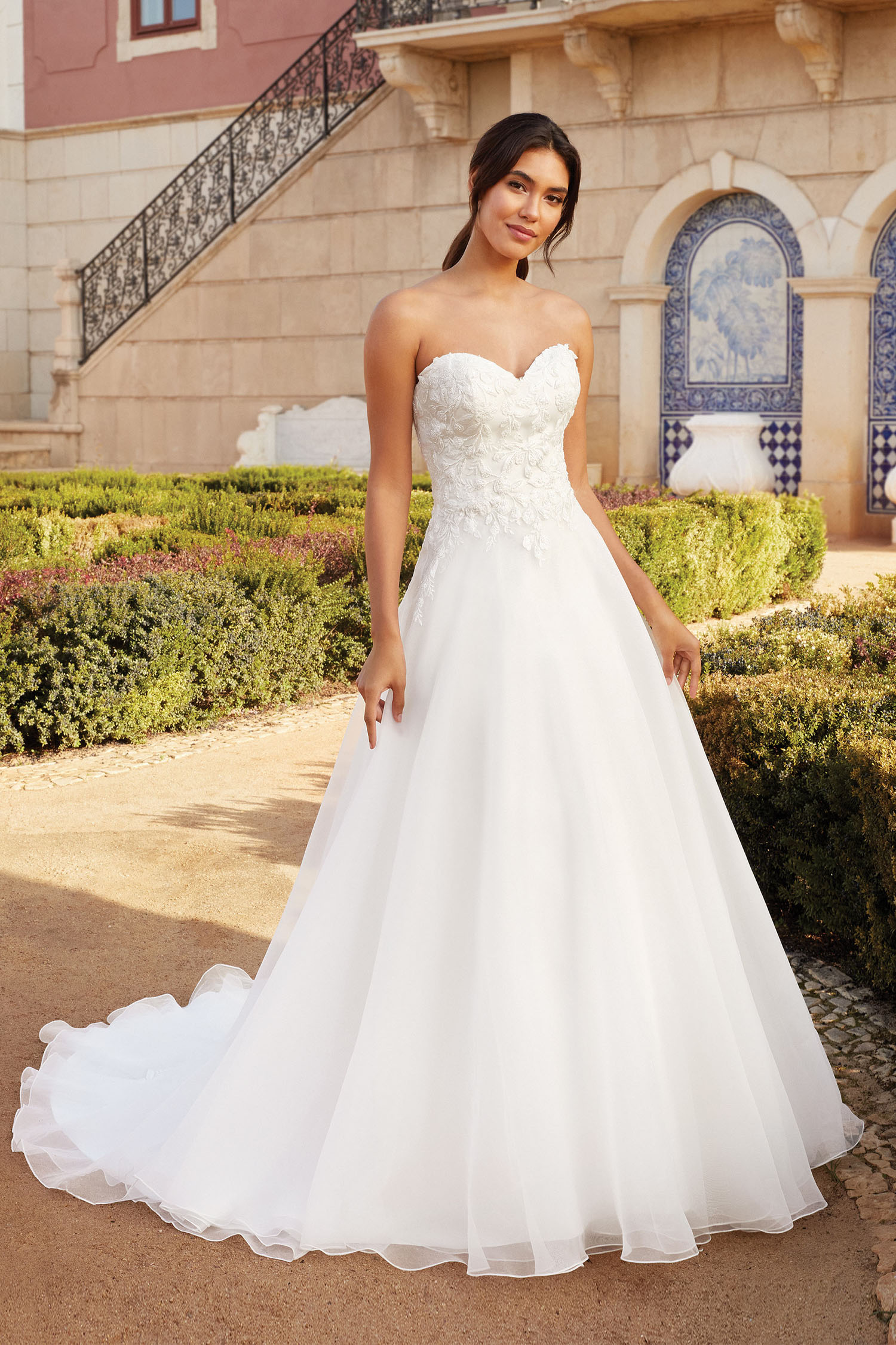Bride wearing an Aline wedding gown with sweetheart neckline and beaded bodice over a full organza skirt.