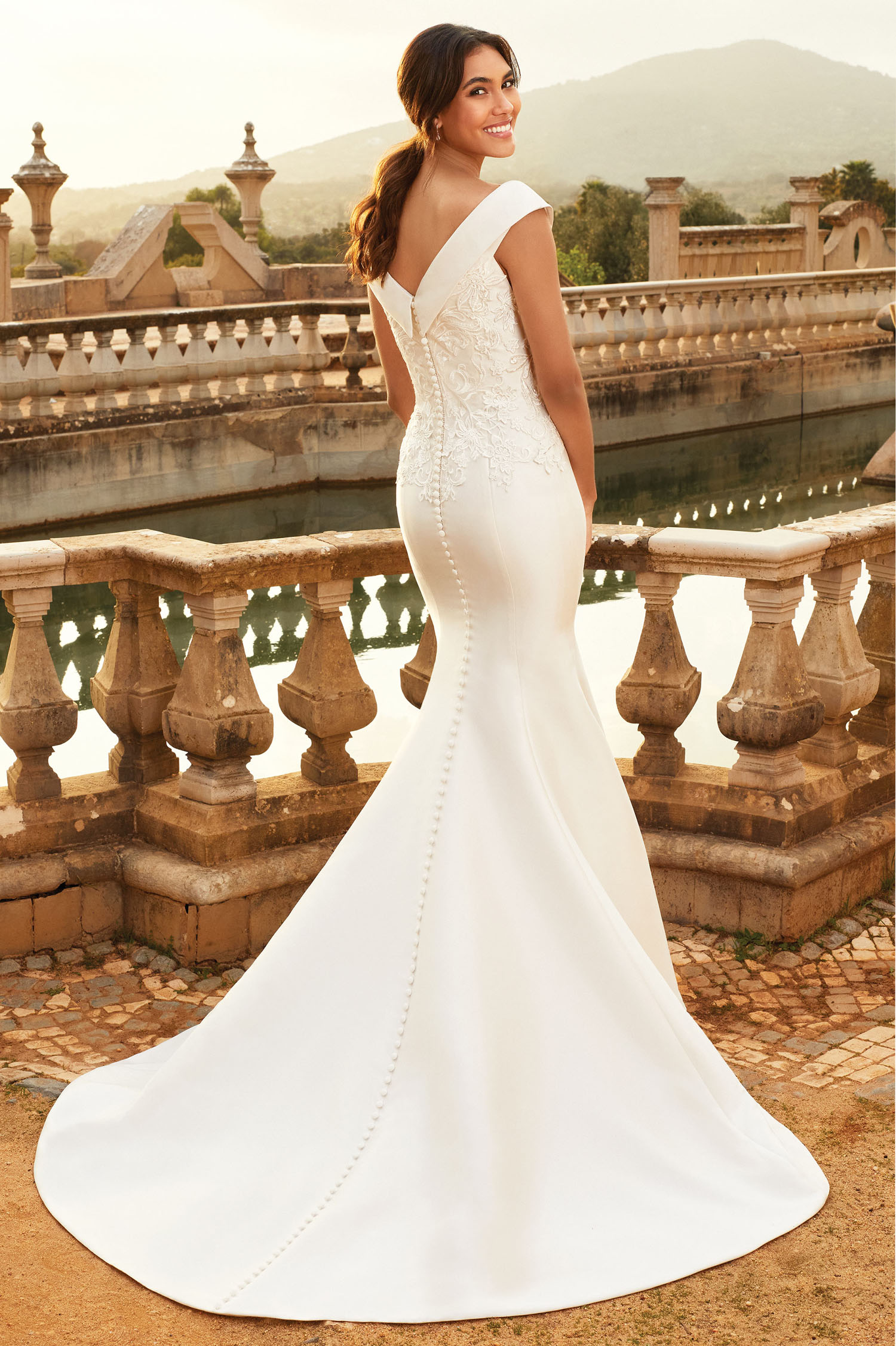 Bride wearing ivory trumpet style gown with bardot neckline.
