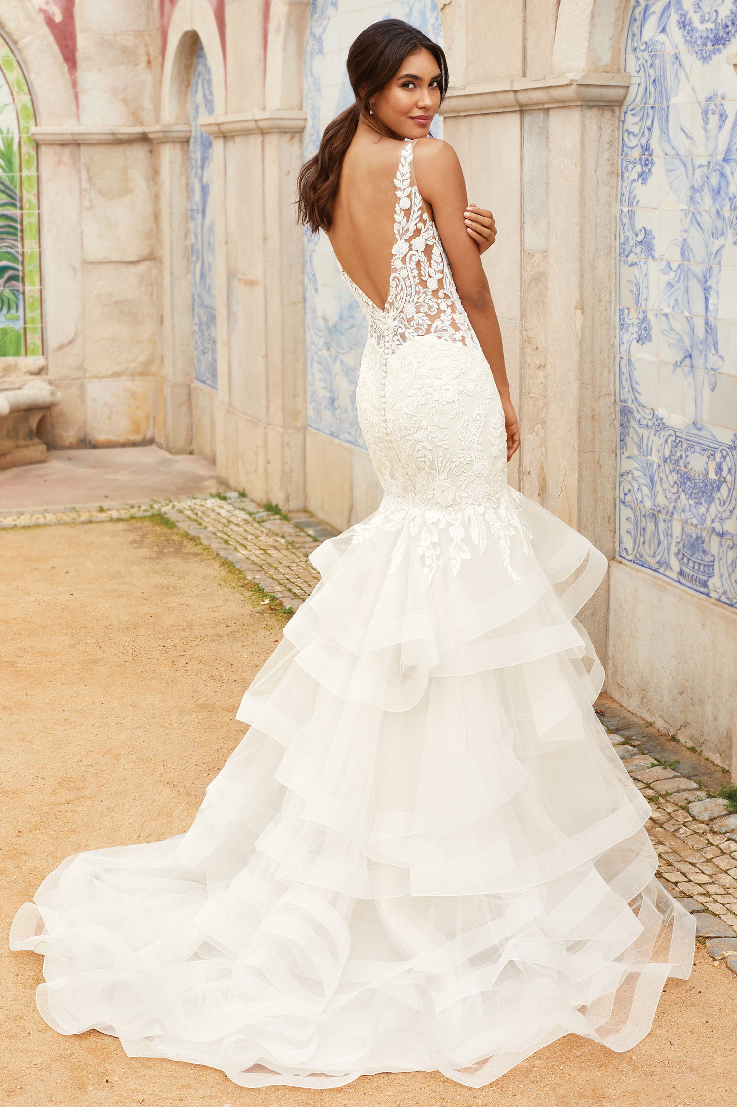 Bride wearing figure hugging fishtail gown with tiered skirt