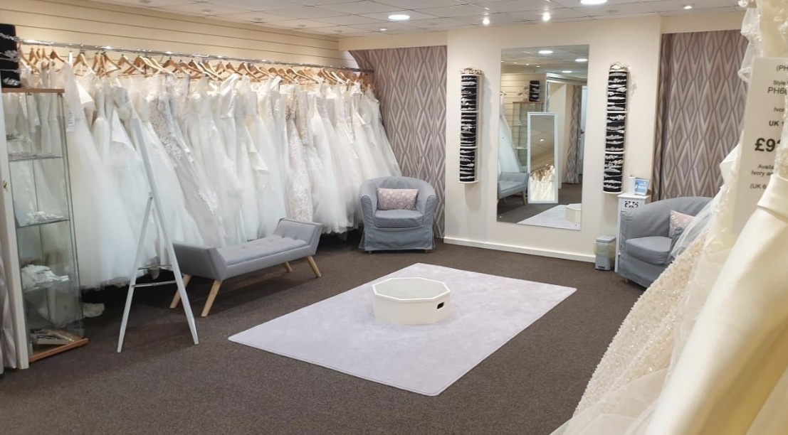 Bridal store interior, with gown rails and large mirror.