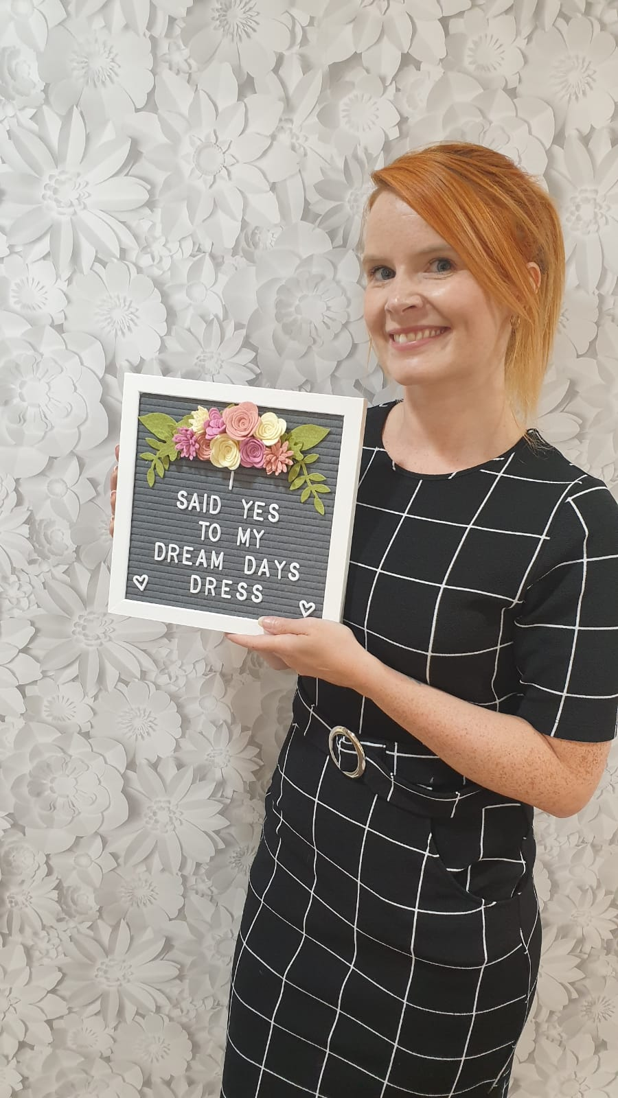 Bride holing a sign to say that she has said yes to her chosen bridal gown.