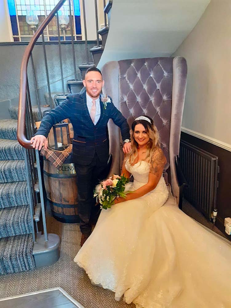 Bride and groom posing for a picture in the hallway at their hotel