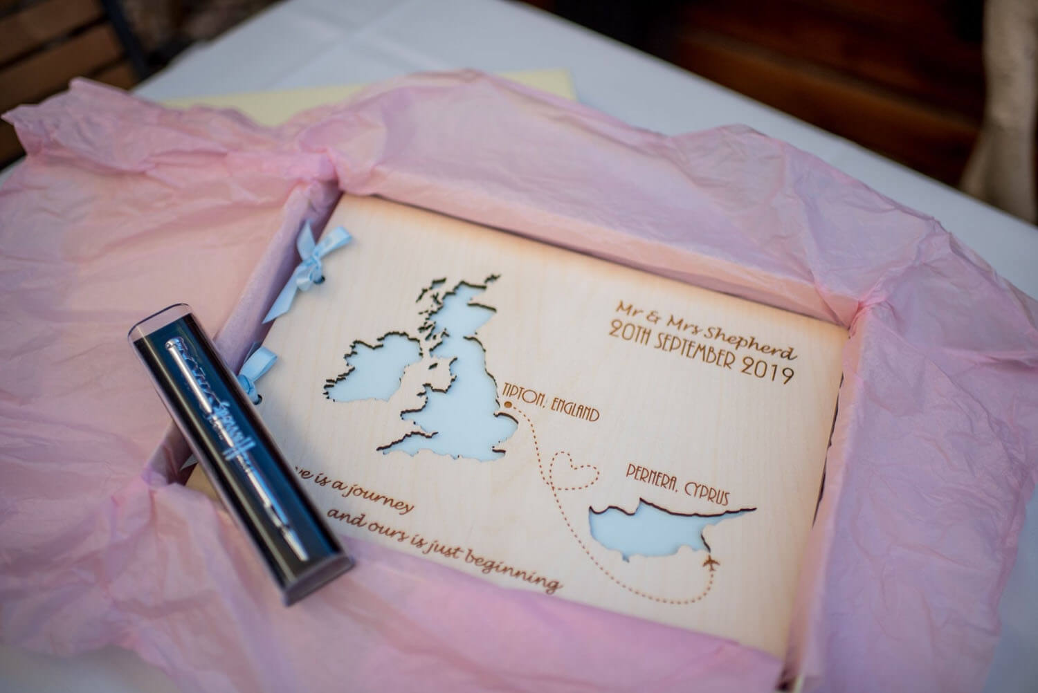 A wooden wedding guest book depicting the UK and Cyprus there the couple got married.