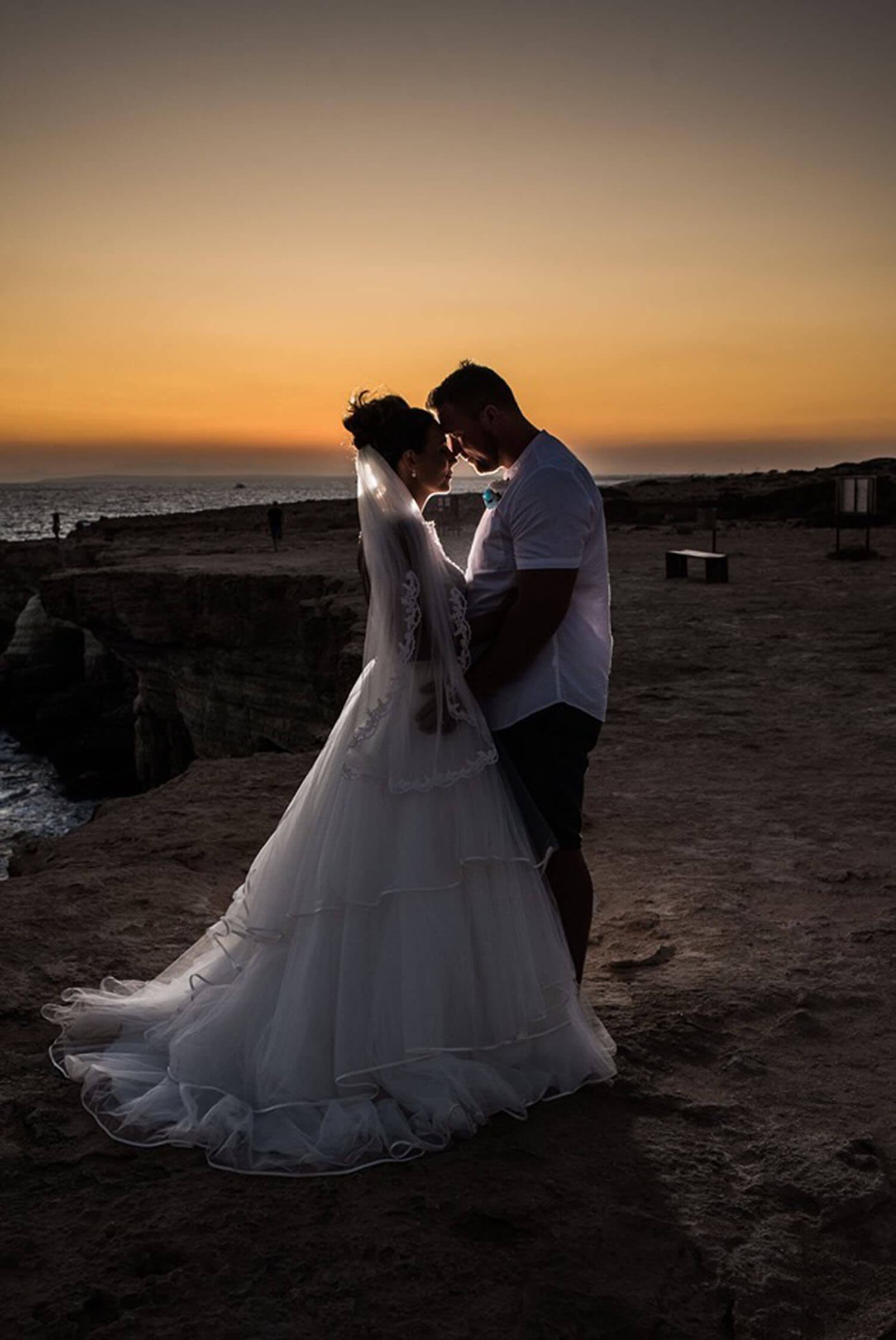 Bride and Groom standing near the sea at sunset.