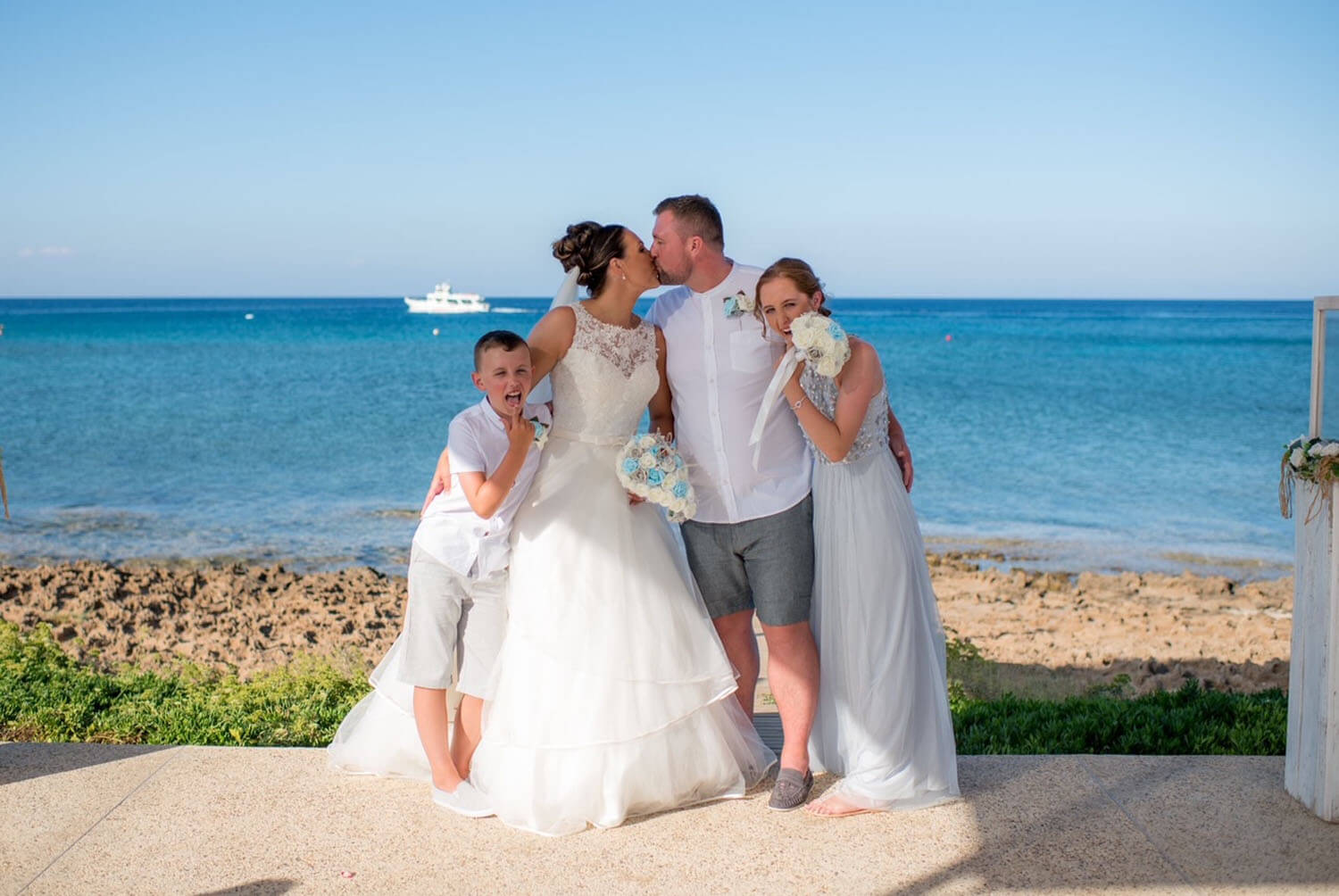 Bride and Groom with their children at the seashore in Cyprus