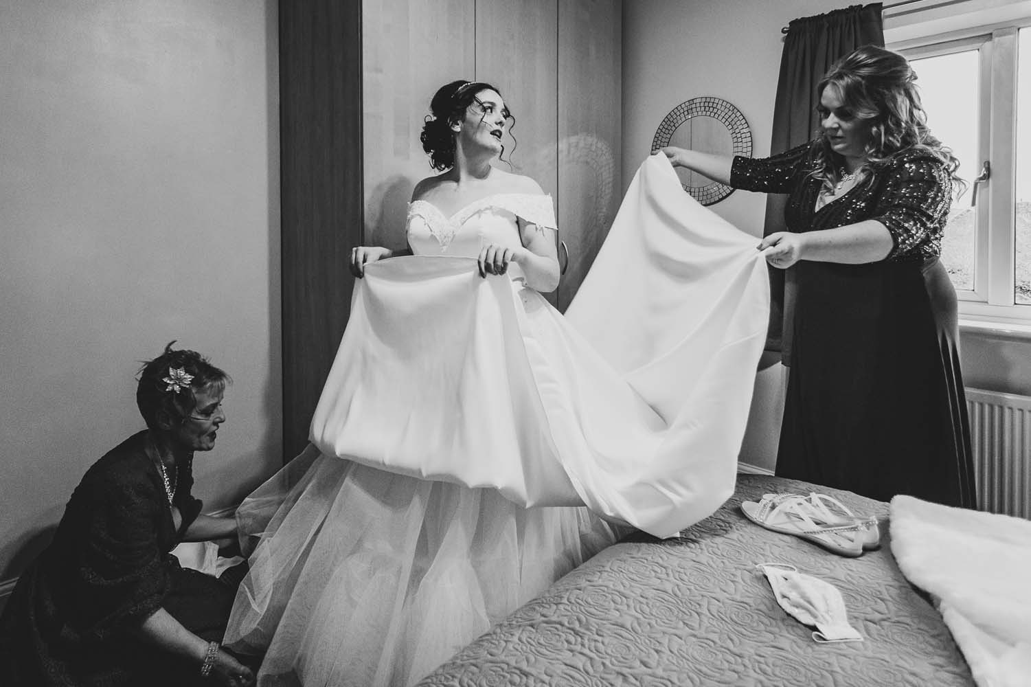 A bride with her Mother and bridesmaid getting ready or the cermony.