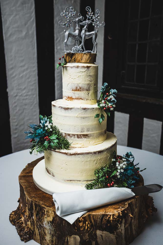 3 tier wedding cake with semi nude decoration and silver stags on the top.