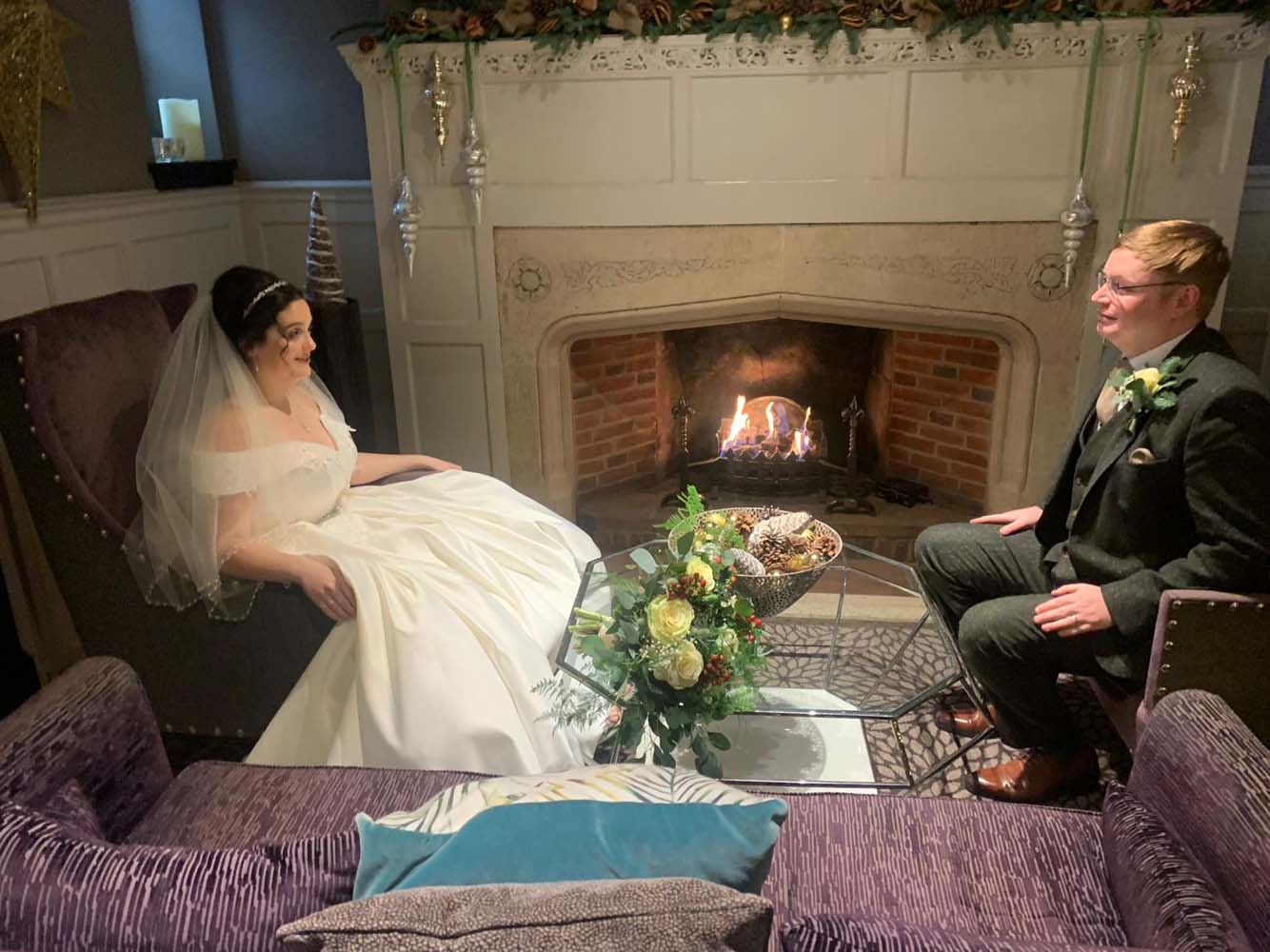 A bride and groom sitting infron of a roarng open fire.