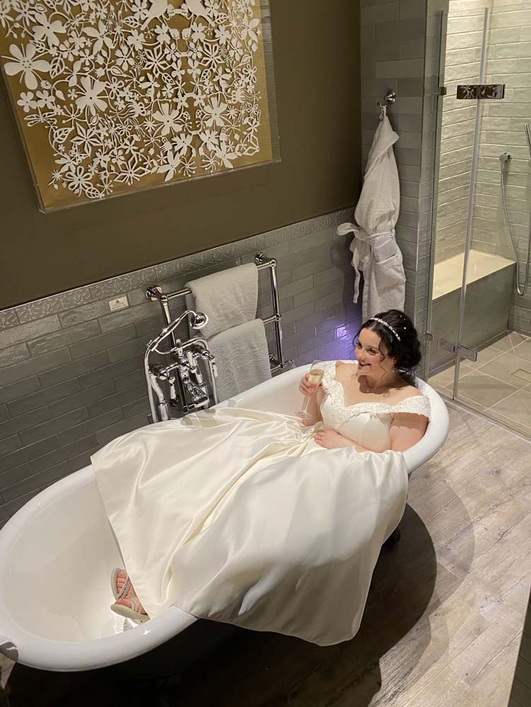 A bride in full wedding attire sitting in the bath of her bridal suite.