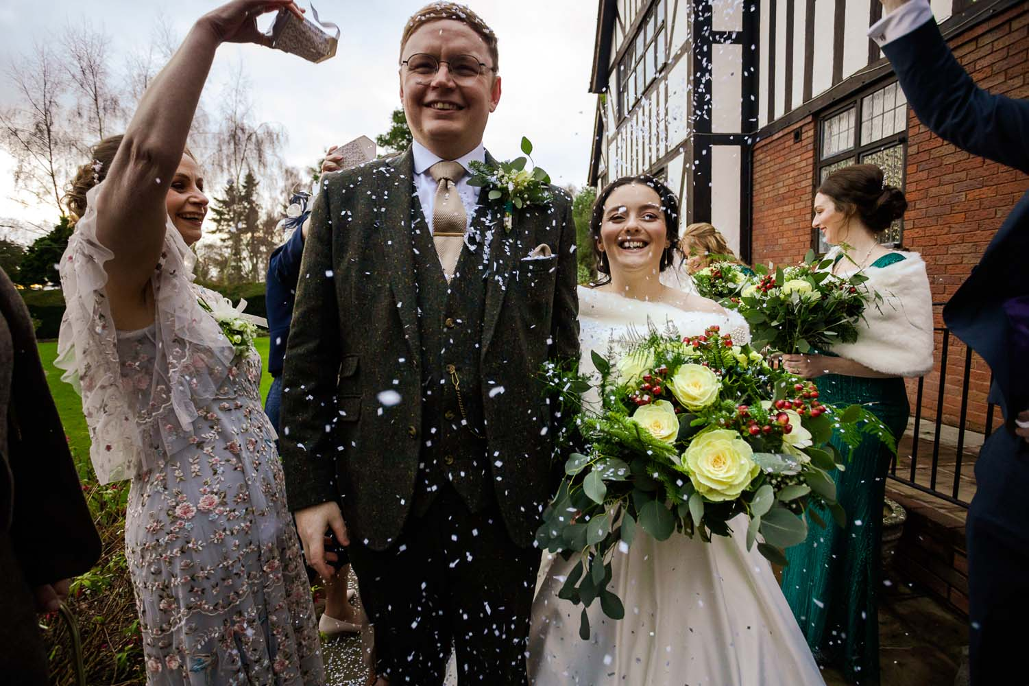 A Bride and Groom walking through their guests having confetti scattered over them.