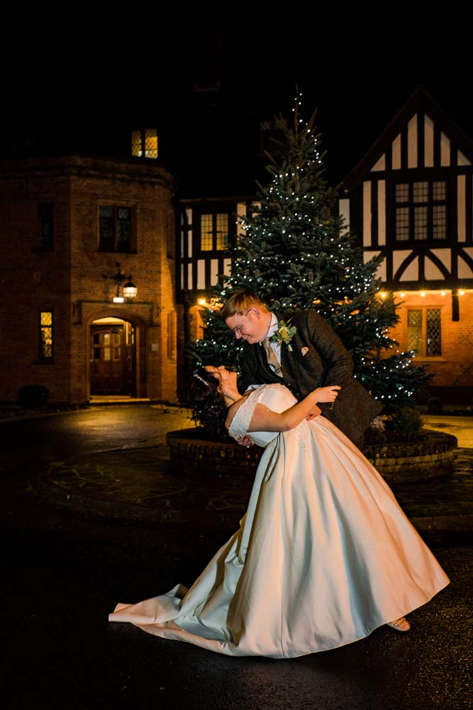 Bride and groom embraced infront of a Christmas tree.