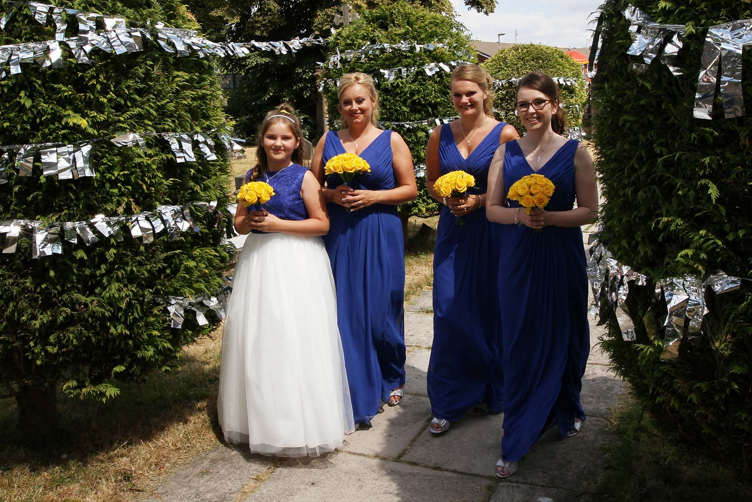 3 bridesmaids and a flower gil in royal blue dresses with lemon posies.