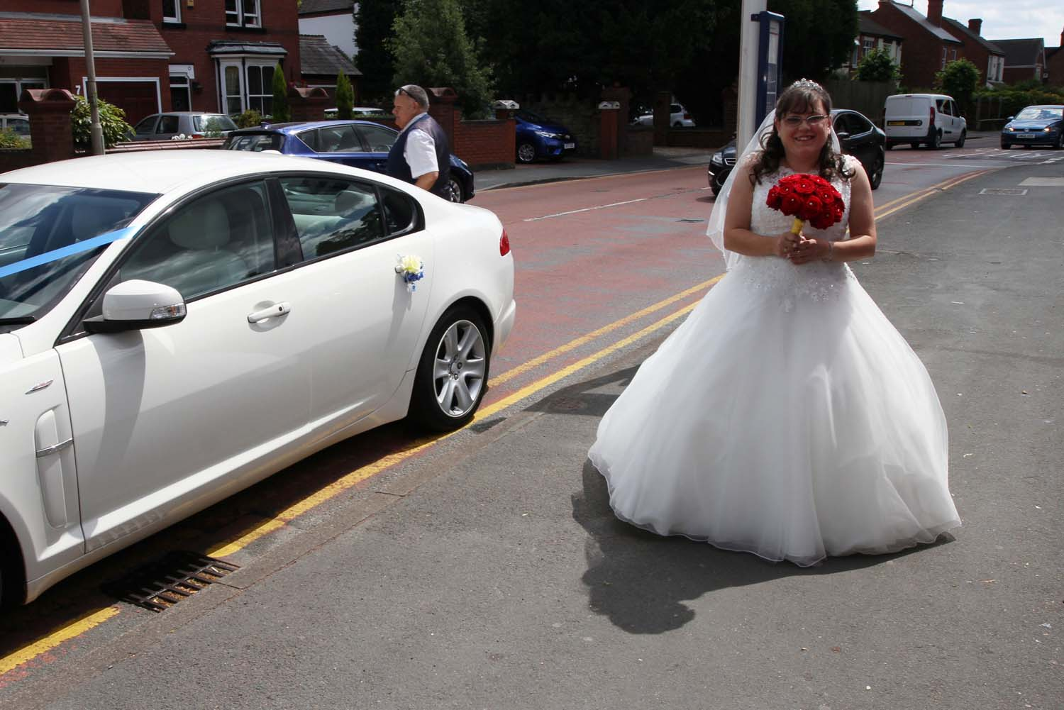 Bride arriving in style in her white wedding car.