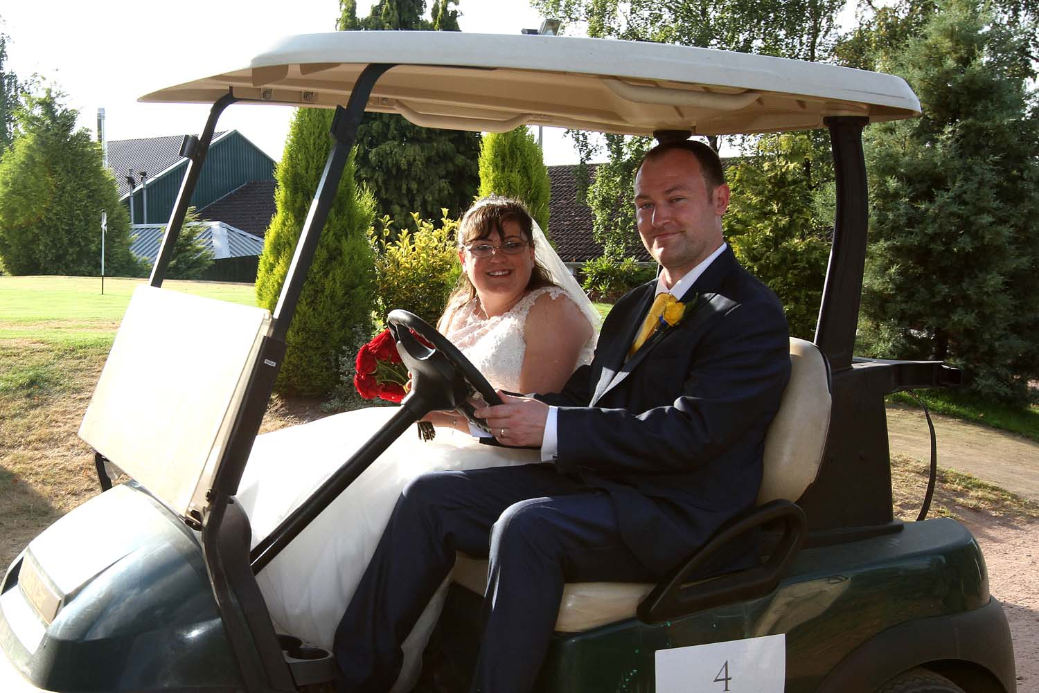 Bride and Groom taking a ride in a golf buggy.